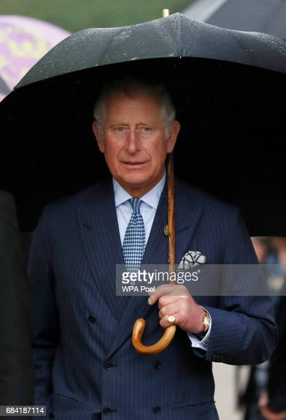 Prince Charles Prince of Wales holds an umbrella as he tours the gardens during a visit to the Royal Botanic Gardens on May 17 2017 in London England...