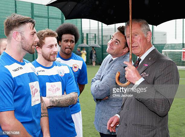 Prince Charles Prince of Wales holds his umbrella as Anthony McPartlin shelters under it as they meet young offenders taking part in a 'Get Started...