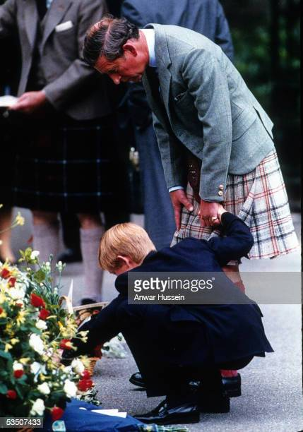 Prince Charles Prince of Wales holds the hand of Prince Harry as they view bouquets of flowers left in memory of Diana Princess of Wales in this...