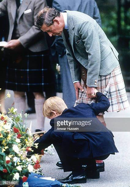 Prince Charles Prince of Wales holds the hand of Prince Harry as they view bouquets of flowers left in memory of Diana Princess of Wales in September...