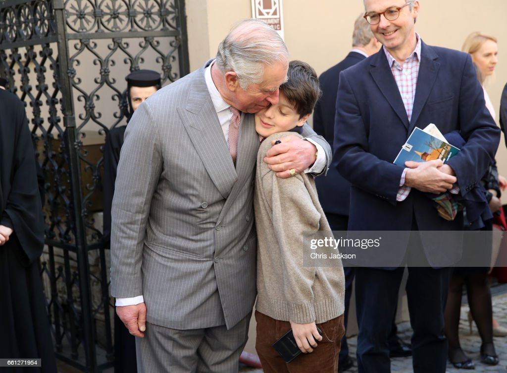Prince Charles, Prince of Wales hugs Valentin Blacker, son of William Blacker (R) who is a local conservationist during a walking tour of the Old Town on the third day of his nine day European tour on March 31, 2017 in Bucharest, Romania. The Monuments Ambulance is a pilot restoration project supported by William Blacker.