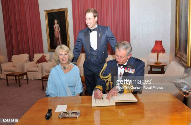 Prince Charles Prince of Wales in his role as Air Chief Marshal Camilla Duchess of Cornwall and Prince William sign the visitor's book after...