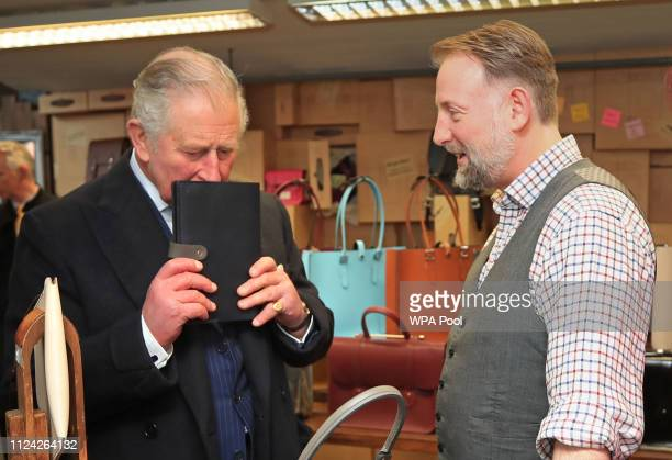 Prince Charles Prince of Wales is given the present of an organiser and a handbag for Camilla Duchess of Cornwall by Keith Hanshaw from The Leather...