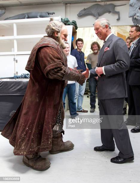 Prince Charles, Prince of Wales is handed a birthday card as he meets Mark Hadlow who plays Dori in the new 'Hobbit' film at Weta Workshop on...