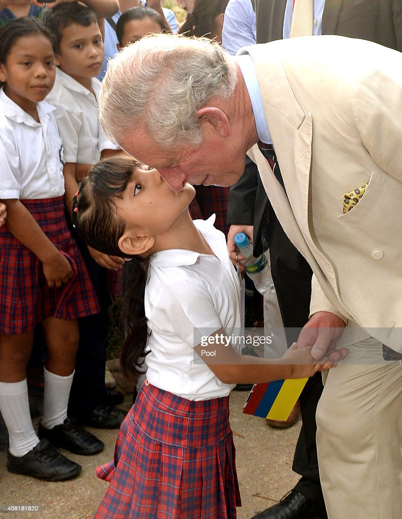 Prince Charles, Prince of Wales is kissed by a local school girl after he and the President of Colombia Juan Manuel Santos visited La Macarena Church on October 30, 2014 in La Macarena, Colombia. The Royal Couple are on a four day visit to Colombia as part of a Royal tour to Colombia and Mexico. After fifty years of armed conflict in Colombia the theme for the visit is Peace and Reconciliation.