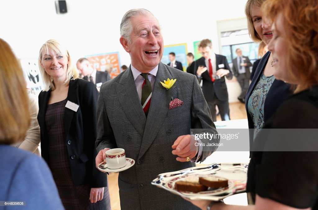 Prince Charles, Prince of Wales is offered traditional Welsh Bara Brith after meeting pupils and teachers involved in a climate change education programme run by the charity, Size of Wales, at Blenheim Road Community Primary, on February 24, 2017 in Cwmbran, United Kingdom.
