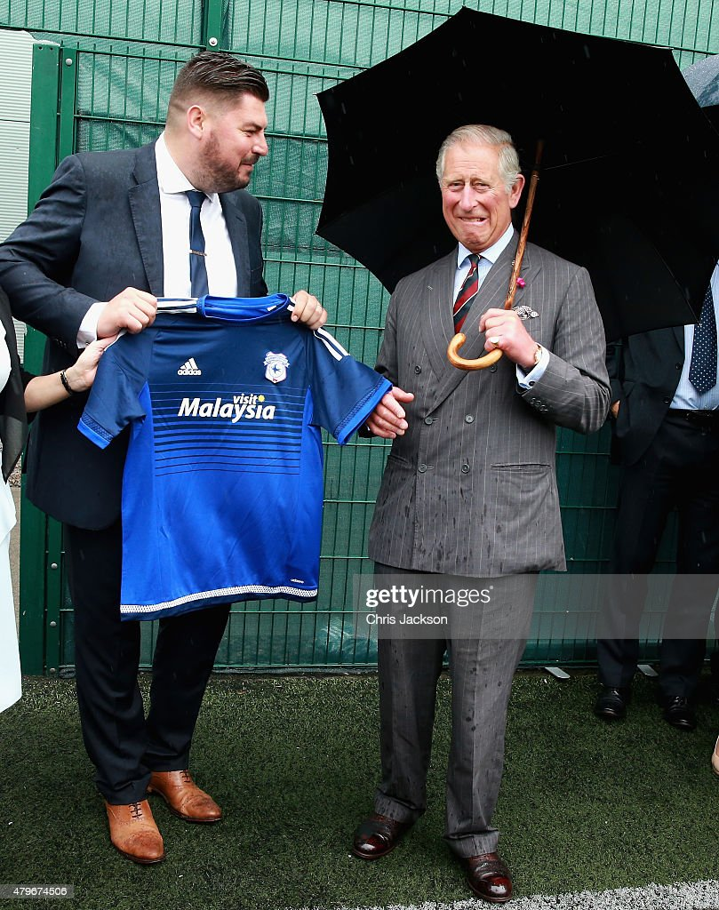 Prince Charles, Prince of Wales is presented with a Cardiff City football shirt after meeting young offenders taking part in a 'Get Started with Football' programme run by the Prince's Trust during a visit to Parc Prison on July 6, 2015 in Bridgend, Wales. HM Prison and YOI Parc expanded earlier this year to become the largest prison in England and Wales with a capacity of 1,705 convicted male adult prisoners and remand/convicted young offenders. It is a category B local prison, which opened in 1997 and is managed by G4S.