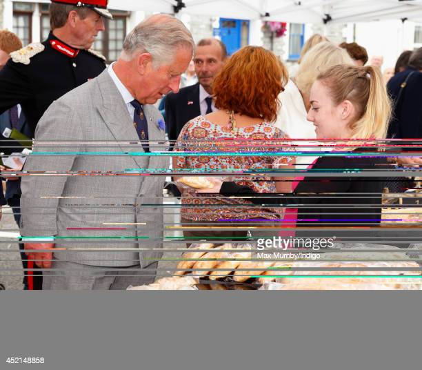 Prince Charles Prince of Wales is presented with a Cornish Pasty as he and Camilla Duchess of Cornwall tour a market on day one of their annual visit...