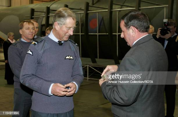 Prince Charles Prince of Wales is presented with a lapel pin by Glan Evans the instructor who taught him to parachute jump 28 years ago during a...
