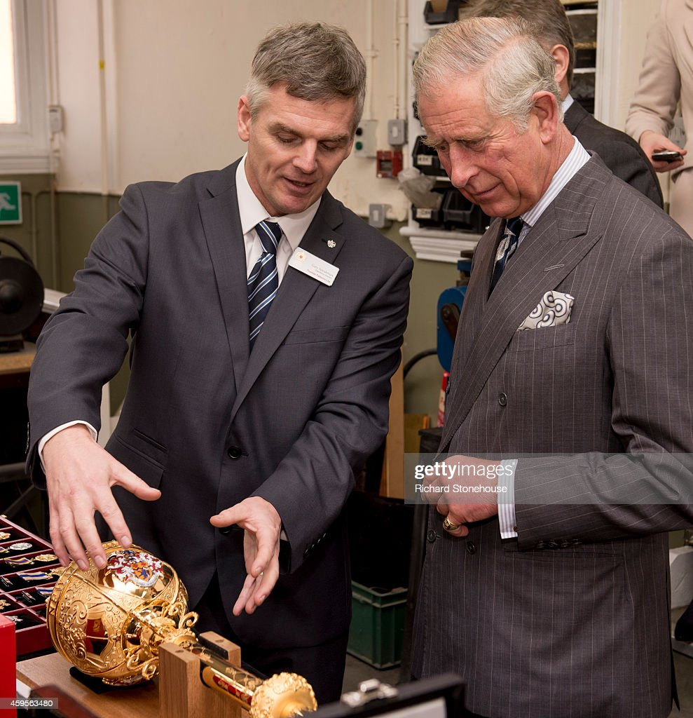 Prince Charles, Prince of Wales is shown examples of work by Operations Director Gary Speakman as he visits Thomas Fattorini Ltd, gold and Silversmiths in Birminghams Jewellery Quarter who make medals and badges including Honours such as the MBE and CBE on November 25, 2014 in Birmingham, England.
