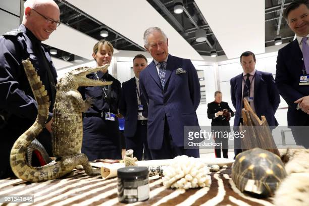 Prince Charles Prince of Wales is shown items of luggage that have been confiscated during inspections by customs officers during a visit to Heathrow...