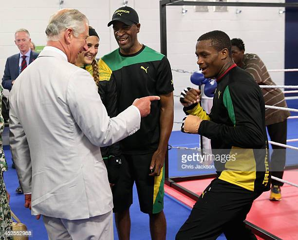 Prince Charles, Prince of Wales jokingly spars with a member of the Jamaican Commonwealth Boxing Team as he visits the Emirates Arena and Chris Hoy...