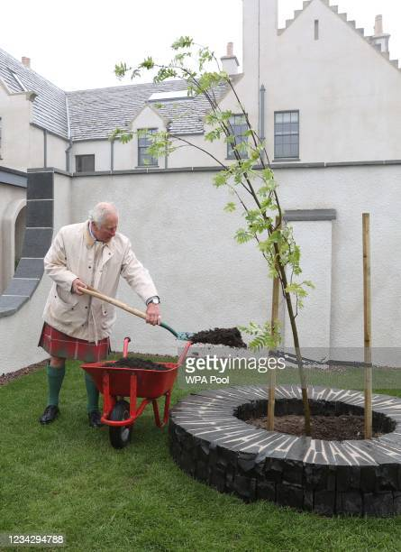 Prince Charles, Prince of Wales, known as the Duke of Rothesay when in Scotland, plants a tree during a tour of the newly-restored House of the...