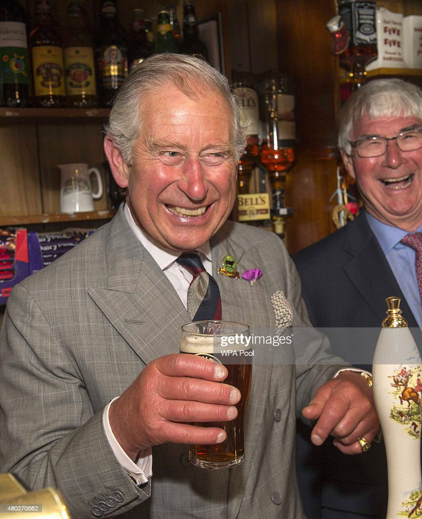 Prince Charles, Prince of Wales laughs as he pulls a pint during a visit to the Glan yr Afon Arms, which is supported by The Prince's Pub is the Hub initiative on July 10, 2015 in Talgarreg, Wales.