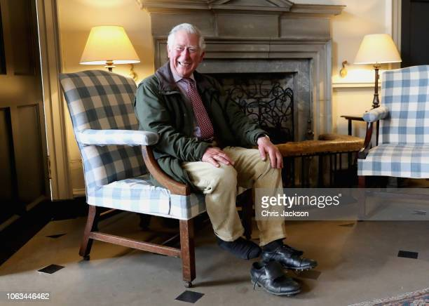 Prince Charles, Prince of Wales laughs as he takes off his boots after an afternoon walk around the grounds of Dumfries House on May 3, 2018 in...