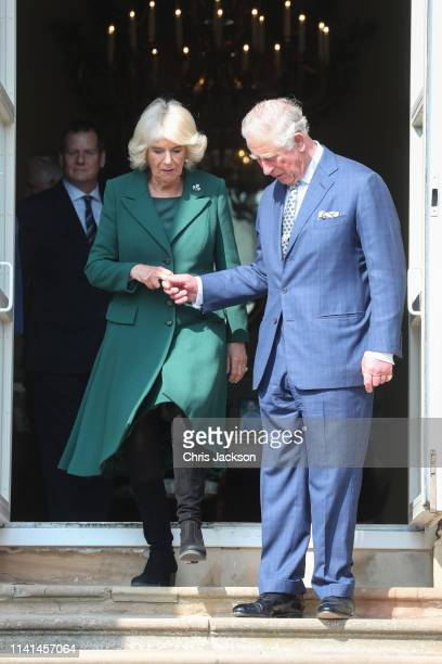 Prince Charles Prince of Wales lends a hand to Camilla Duchess of Cornwall during the reopening of Hillsborough Castle on April 09 2019 in Belfast...