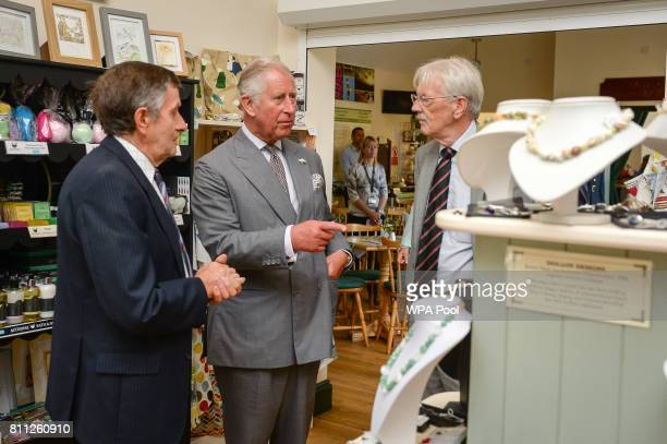 Prince Charles Prince of Wales look around the giftshop before he unveils a new stained glass window on the theme of Welsh legends created by local...