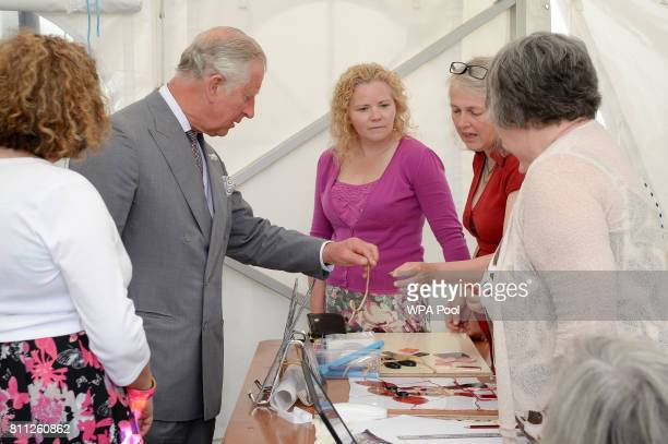 Prince Charles Prince of Wales looks at cooper tape used to make stained glass art before he goes to unveil a new stained glass window on the theme...