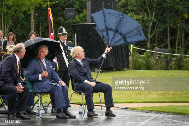 Prince Charles, Prince of Wales looks on as British Prime Minister, Boris Johnson opens his umbrella at The National Memorial Arboretum on July 28,...