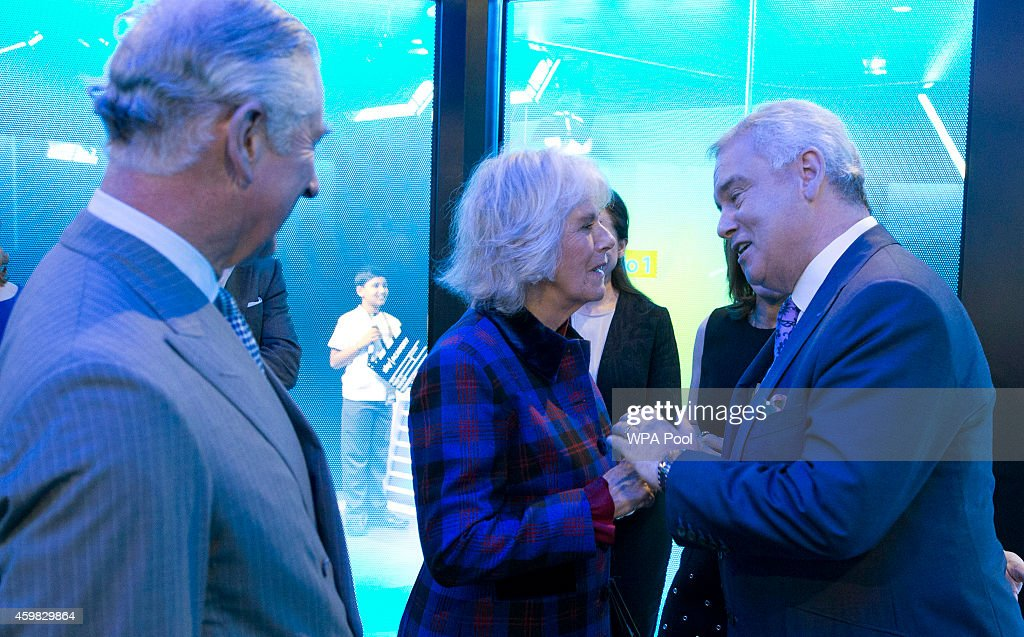 Prince Charles, Prince of Wales looks on as his wife Camilla, Duchess of Cornwall is greeted by TV presenter Eamonn Holmes during a visit to Sky on December 2, 2014 in London, England.