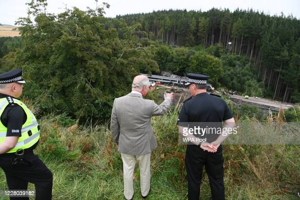 Prince Charles Prince of Wales looks over at the scene of the ScotRail train derailment near Stonehaven Aberdeenshire which cost the lives of three...