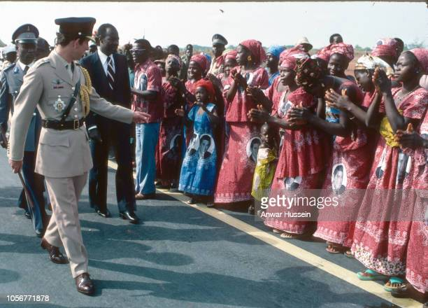 Prince Charles Prince of Wales meets some of his fan club wearing dresses with his picture as he arrives in the Ivory Coast on March 01 1977 in the...