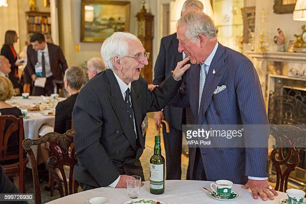 Prince Charles Prince of Wales Patron of The Battle of Britain Fighter Association speaks with Flight Officer Ken Wilkinson as they host a tea for...