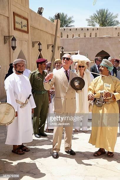 Prince Charles Prince of Wales performs a traditional sword dance with local Omanis as Camilla Duchess of Cornwall looks on as they visit Nizwa Fort...