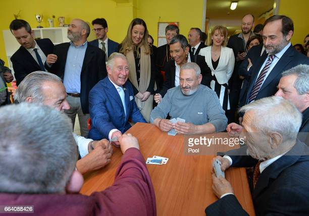 Prince Charles Prince of Wales plays cards with a group of residents at the Caritas refugee centre during day 4 of their visit to Italy on April 3...