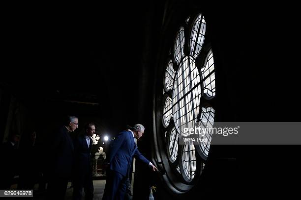Prince Charles Prince of Wales points as he looks at works taking place beside a window flanked by the Dean of Westminster John Hall left during his...
