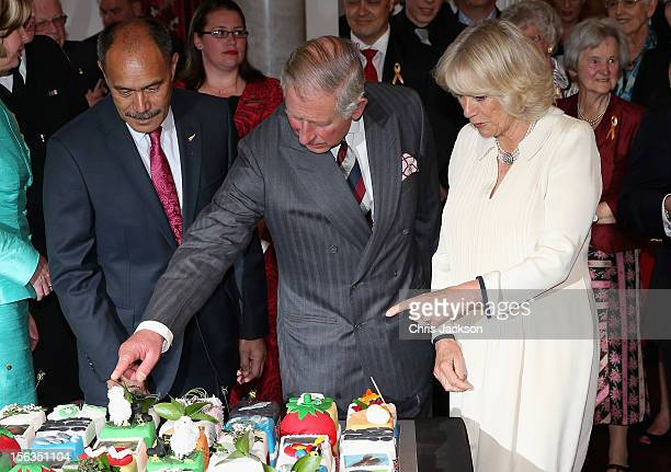 Prince Charles Prince of Wales points to a sheep on his 64th birthday cake with Sir Jerry Mateparae GovernorGeneral of New Zealand at Government...