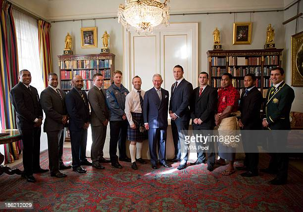 Prince Charles Prince of Wales poses for a group photograph with representatives from teams competing in the Rugby League World Cup during a...