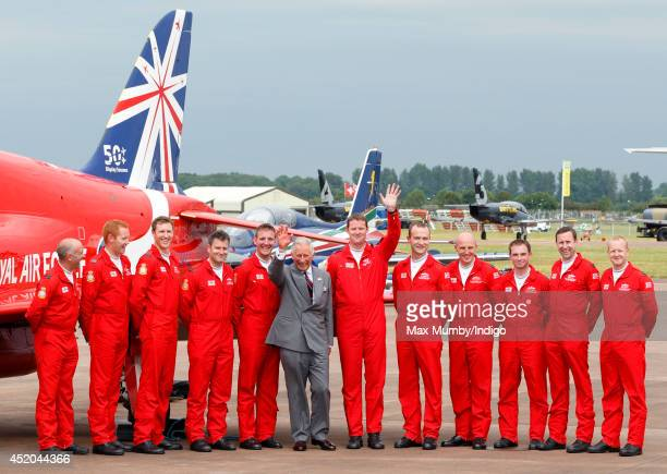 Prince Charles, Prince of Wales poses for a photograph with pilots of the RAF Aerobatic Team, The Red Arrows as he visits the Royal International Air...