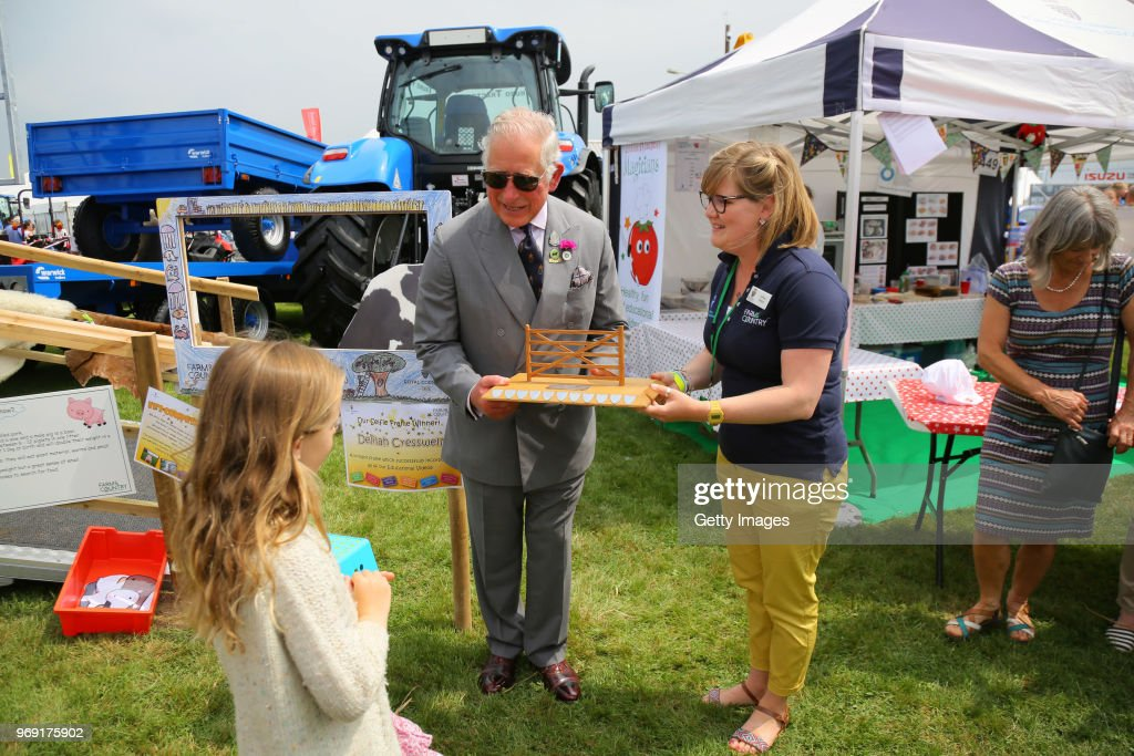 Prince Charles, Prince of Wales (Patron of the Royal Cornwall Agricultural Association) presents Delilah Cresswell, winner of the selfie frame competition, that will link 6 of the show's educational videos together, with her award as he attends the Royal Cornwall Show on June 7, 2018 in Wadebridge, England.