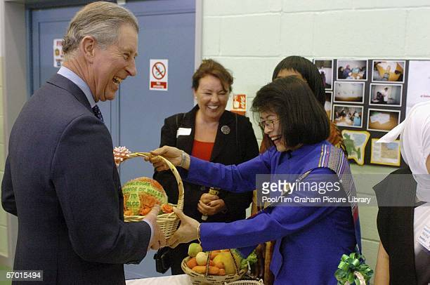 Prince Charles Prince of Wales President of Business in the Community and The Prince's Trust is given a carved watermelon as a gift by Siriphan...