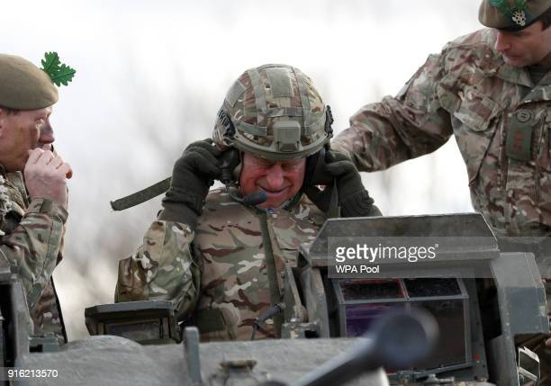 Prince Charles Prince of Wales puts on a helmet before he rides on a Warrior Tracked Armoured Vehicle during a training exercise on a visit to The...