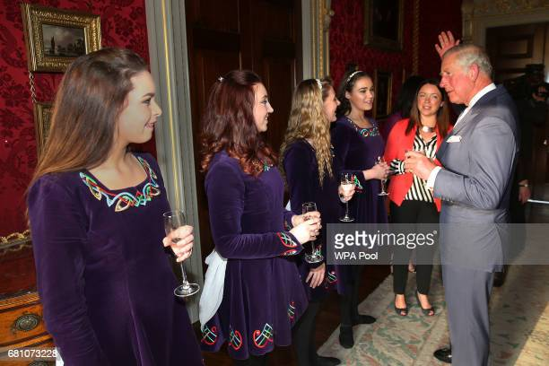 Prince Charles Prince of Wales raises his hand as he discusses Irish dancing techniques with the Tir na NOg Irish Dancers leftright Sarah White Rose...