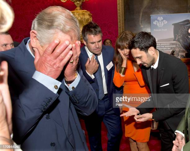 Prince Charles Prince of Wales reacts as magician Dynamo demonstrates the flexibility of his fingers as Kenny Logan and Carol Voderman look on at a...