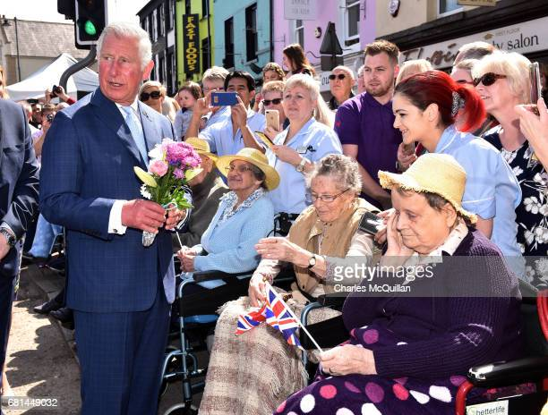 Prince Charles Prince of Wales receives a bunch of flowers as they visit the village market on May 10 2017 in Dromore Northern Ireland Their Royal...