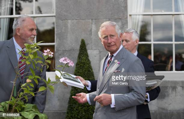 Prince Charles Prince of Wales receives a gift from Anthony Tavernor owner and restorer of the Plas Cadnant Hidden Gardens as he vists the gardens...