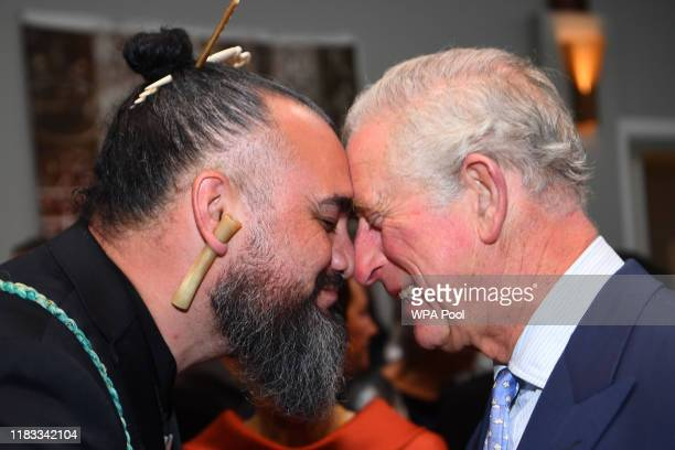 Prince Charles Prince of Wales receives the hongi the traditional Maori greeting from musician Horomona Horo during a reception hosted by...