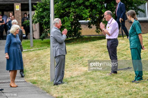 Prince Charles, Prince of Wales remains socially distanced as he a performs a namaste to Professor Mark Pietroni as he arrives with Camilla, Duchess...