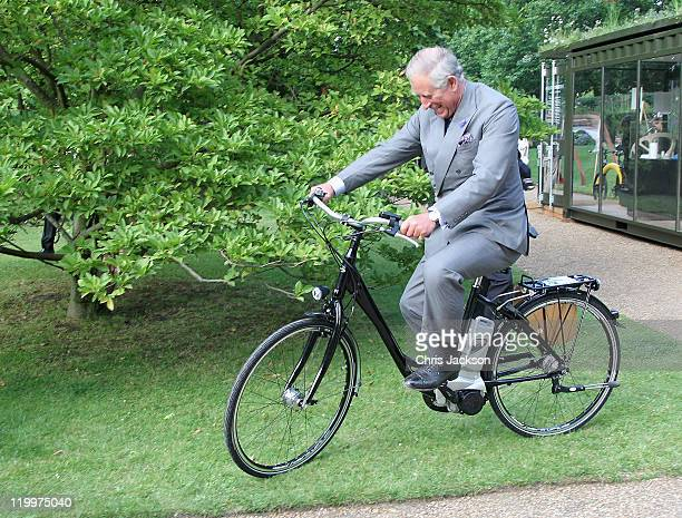 Prince Charles Prince of Wales rides an ecobike as he attends a preview of Start Day which features exhibits from the Earth Awards at Clarence House...