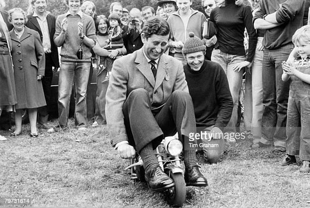 Prince Charles Prince of Wales riding a mini motorbike at Bisley Rifle Range