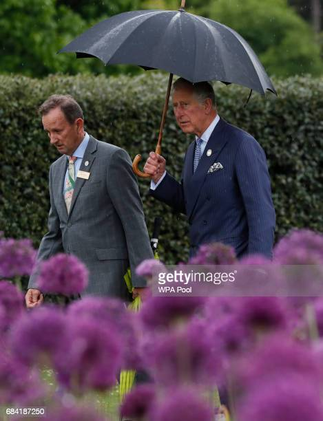 Prince Charles Prince of Wales right walks past a display of alliums tours the Great Broad Walk during a visit to the Royal Botanic Gardens on May 17...