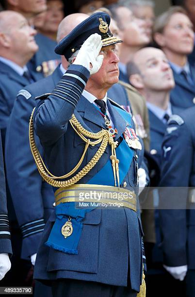 Prince Charles Prince of Wales salutes as he watches a flypast of Spitfire and Hurricane aircraft after attending the Battle of Britain 75th...
