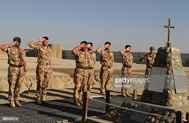 Prince Charles, Prince of Wales saluts during a memorial for British soldiers killed in Helmand at Bastion camp on March 25, 2010 in Helmand...