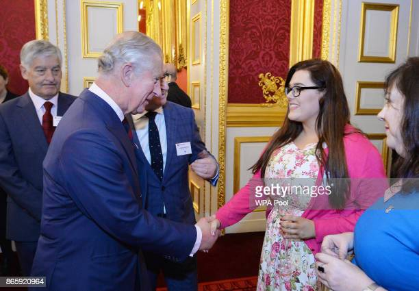 Prince Charles Prince of Wales shakes hands with Amy Weston at a reception for British Red Cross volunteers at St James's Palace on October 24 2017...