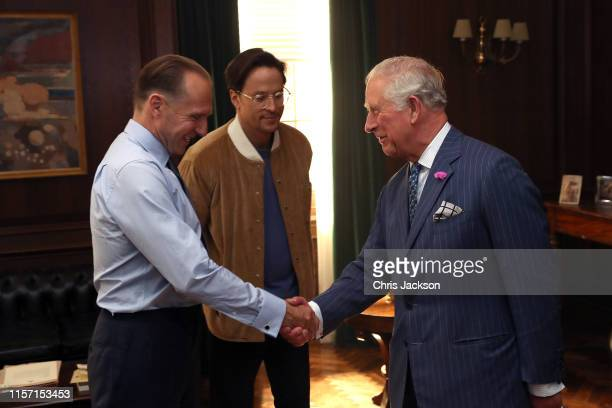 Prince Charles, Prince of Wales shakes hands with Ralph Fiennes and director Cary Joji Fukunaga during a visit to the James Bond set at Pinewood...