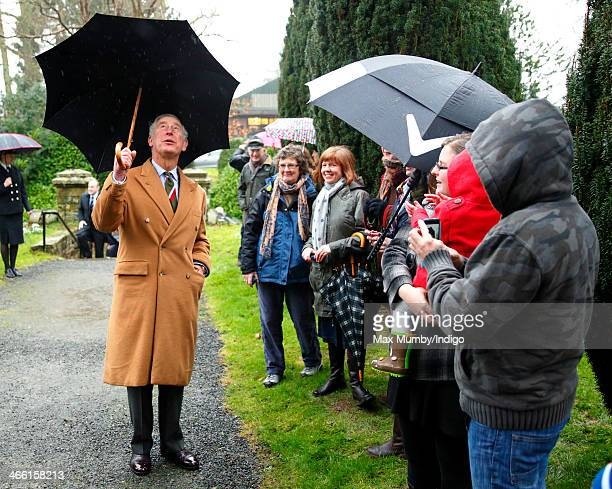 Prince Charles Prince of Wales shelters under an umbrella as he meets members of the public during a visit to The Church of St John the Evangelist in...